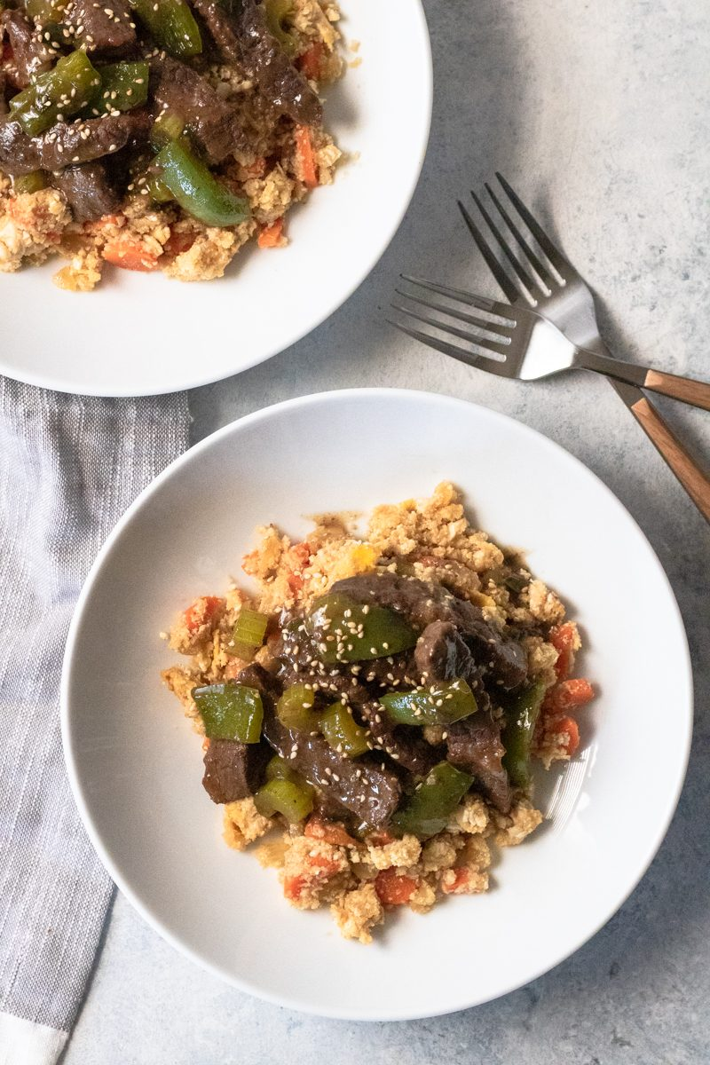 Gluten free, low carb green pepper steak over fried cauliflower rice. It's an amazing paleo and Whole30 compliant meal