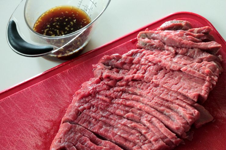 Sliced round steak and marinade for a Paleo, Whole30 green pepper steak dinner