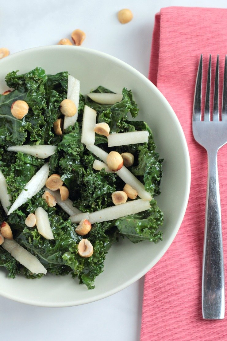 A quick and easy kale lunch salad. Garnished with toasted hazelnuts, pears, and drizzled with a maple dijon dressing
