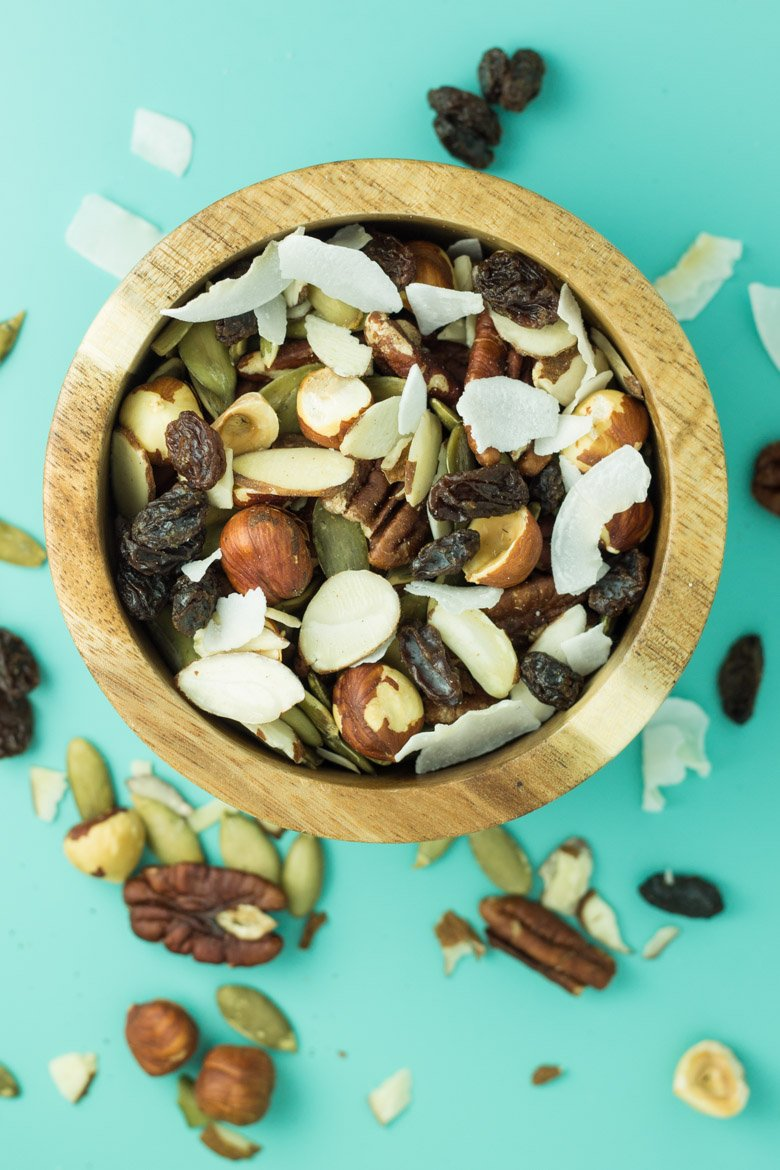 Adding combos of nuts, dried fruit, and shredded coconut flakes is the easiest way to make paleo granola for a perfect portable breakfast