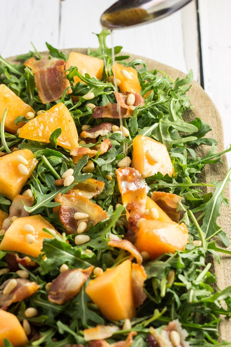 A warm olive oil, bacon, and honey dressing makes this arugula salad with candied cantaloupe simply amazing!