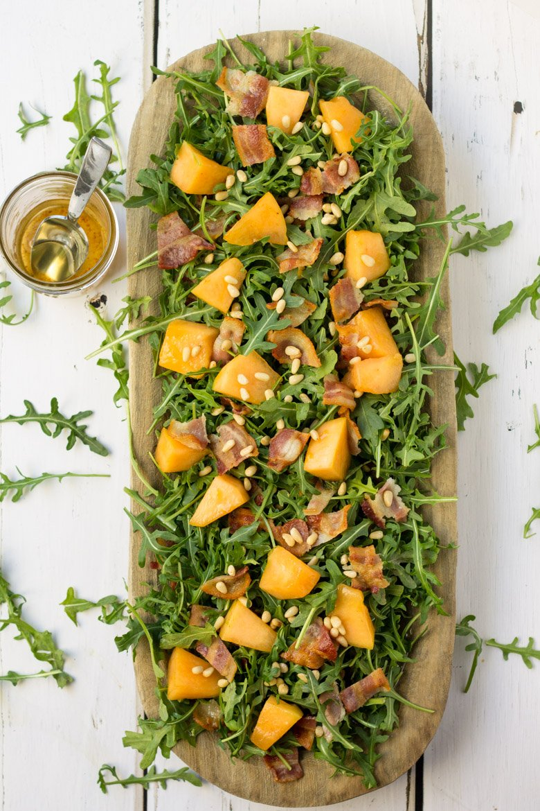 This paleo arugula salad has savory bacon, crunchy pine nuts, and honey-glazed candied cantaloupe. Perfect for parties and a summer BBQ's!