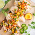 Easy summer dish! Grilled chicken with jalapeño peach salsa is a simple, healthy way to serve chicken breasts with some major flavor. Paleo and Whole30
