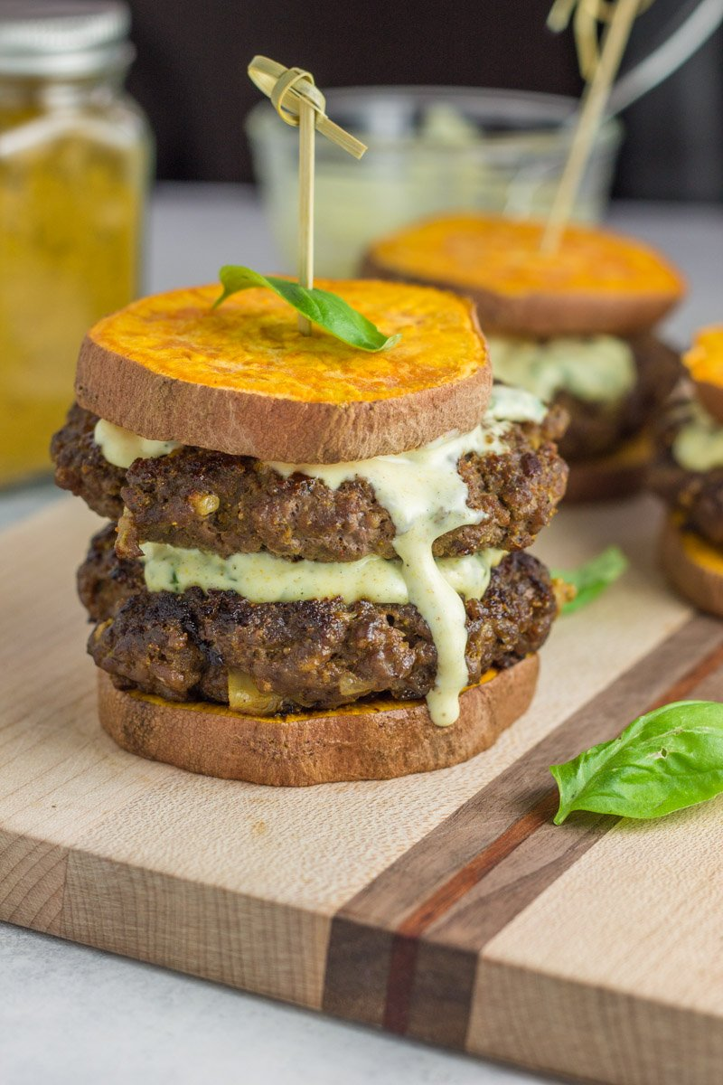 This paleo and Whole30 curried beef burger is topped with the most amazing basil curry aioli. Complete with a sweet potato bun. Made on stovetop or the grill!
