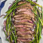 This paleo, Whole30 sheet pan flank steak dinner is paired perfectly with roasted red onions and asparagus