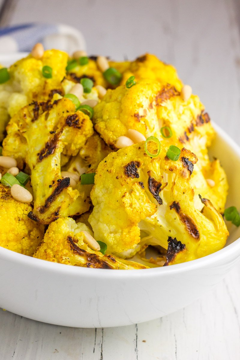 Grilled cauliflower seasoned with turmeric. It's the perfect healthy summer side dish