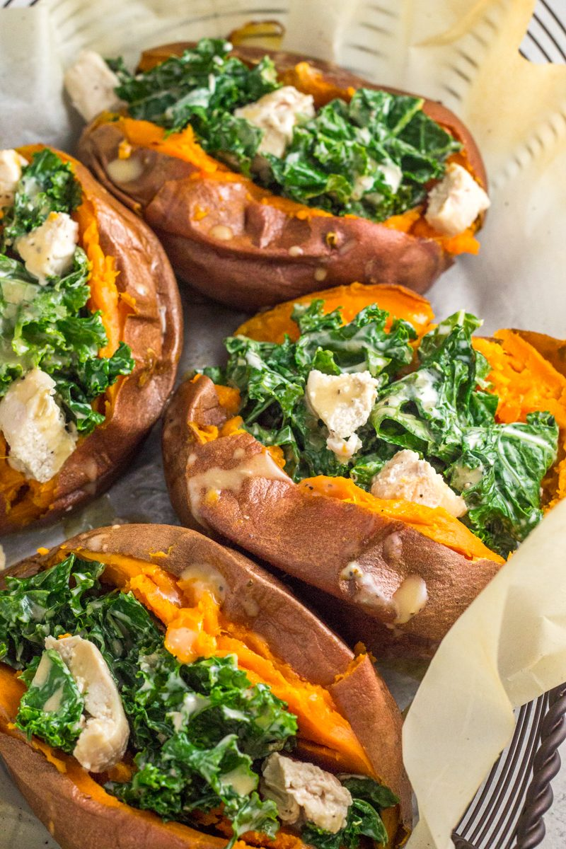 These paleo + Whole30 stuffed sweet potatoes are packed with a warm kale & chicken caesar salad that's to die for!